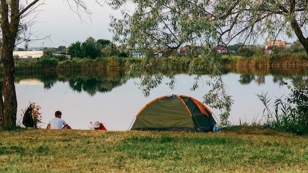 Una tienda de campaña junto al lago en una tarde de verano y dos hombres van a pescar