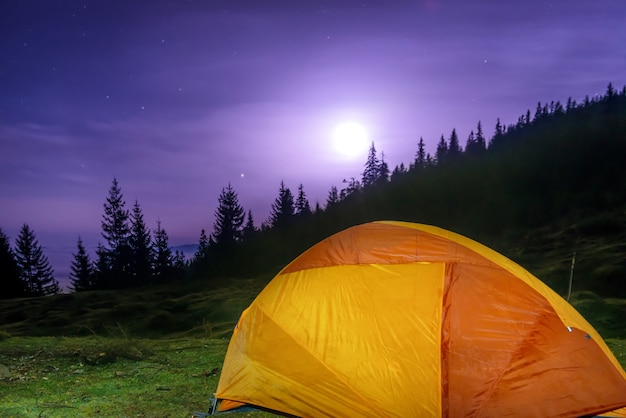 Tienda de campaña naranja iluminada bajo la luna, estrellas en la noche