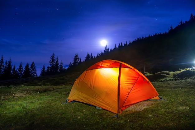 Tienda de campaña naranja iluminada bajo la luna
