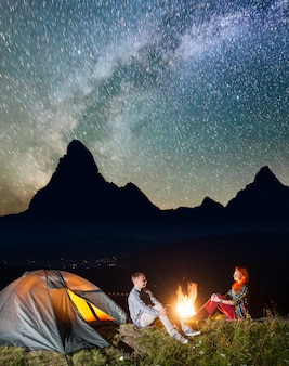 Tienda de campaña nocturna. turistas sentados junto a la fogata bajo el cielo estrellado