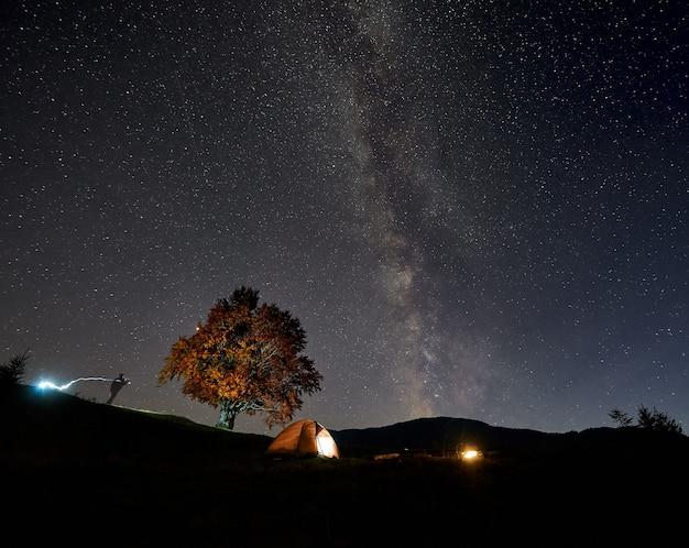 Tienda de excursionistas turísticos iluminada desde el interior, silueta de hombre y fogata ardiente bajo el cielo estrellado azul oscuro.