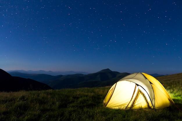 Tienda de excursionistas turísticos en las montañas por la noche con estrellas en el cielo