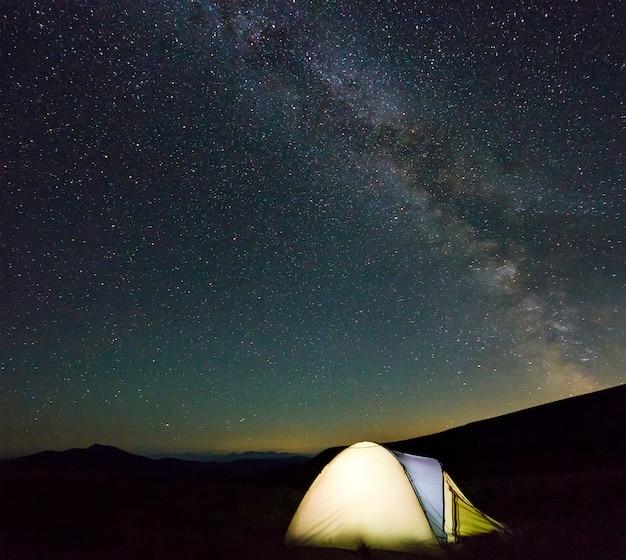 Tienda de excursionistas turísticos en las montañas por la noche con estrellas de la vía láctea en el cielo