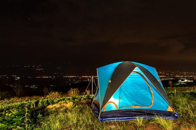 Tienda y fondo de cielo y vistas a la montaña por la noche.