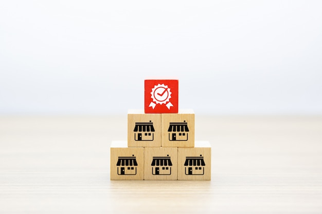 Tienda de iconos de negocios de franquicia en bloque de juguete de madera y símbolo de calidad.