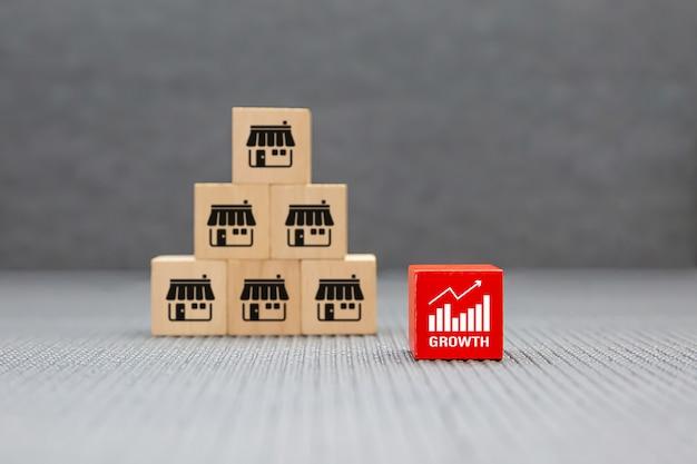 Tienda de iconos de negocios de franquicia en bloques de juguete de madera apilados en forma de pirámide con símbolo gráfico.
