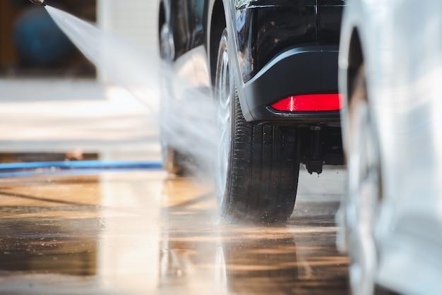 La tienda de lavado de autos está lavando el auto con agua. rocíe agua sobre las ruedas, limpie los automóviles en la estación de lavado