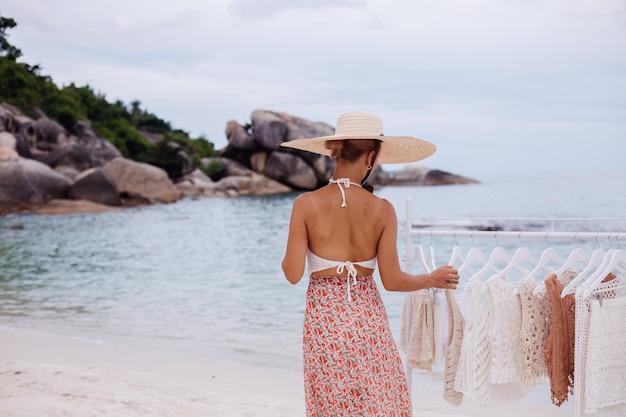 Tienda de playa al aire libre para ropa de punto mujer elección qué comprar del colgador de piso concepto de ropa de punto de verano