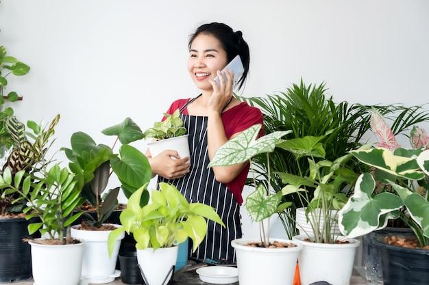 Tienda de propietario de plantas de mujer asiática hablando por teléfono inteligente de pie con plantas vendiendo, obtener un pedido de un cliente, concepto de pequeña empresa
