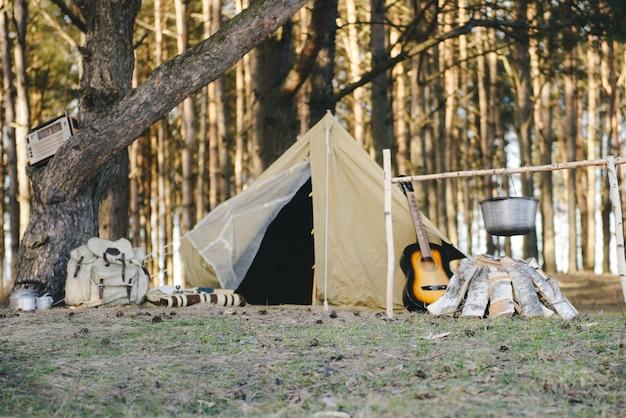 Tienda retro, mochila, guitarra, fuego en el bosque cerca del río