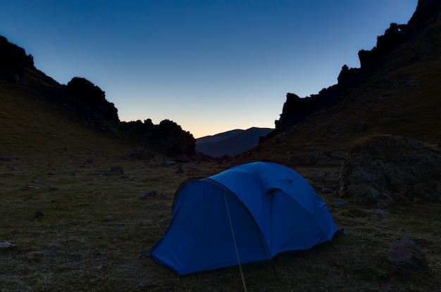 Tienda turística en las montañas durante el crepúsculo vespertino
