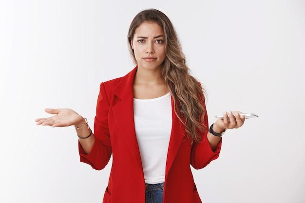 Tienes algún problema. cuestionado molesto atractivo confiado joven caucásico mujer de pelo rizado encogiéndose de hombros consternación insegura sosteniendo las manos del teléfono inteligente extendidas hacia los lados, no puede entender lo que la persona quiere