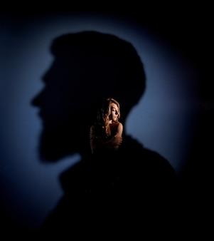 Tierna chica rubia caucásica con los ojos cerrados está de pie en la sombra de la cabeza del hombre en la pared azul