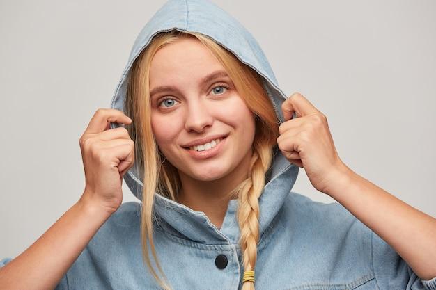 Tierna hermosa joven rubia con trenza, las manos mantienen la capucha, se siente feliz, sonríe a un espectador