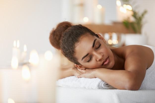 Tierna mujer africana descansando relajante con los ojos cerrados en el salón de spa.