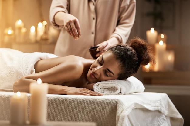 Tierna mujer africana relajante disfrutando de un masaje saludable spa con aceite.