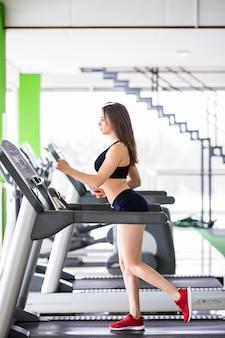 Tierna mujer corre en un simulador deportivo en un moderno gimnasio vestido con ropa deportiva negra