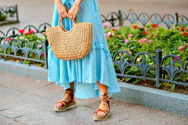 Tierna mujer elegante posando y vistiendo maxi vestido azul, bolso de paja y sandalias de gladiador