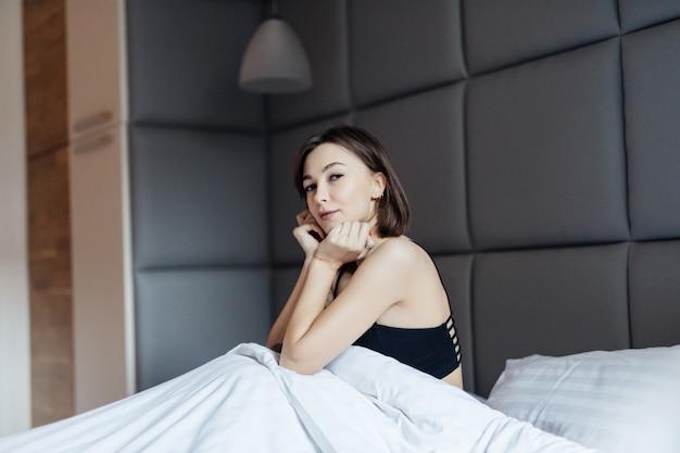 Tierna mujer morena de pelo largo en la cama blanca en la suave luz de la mañana bajo el edredón