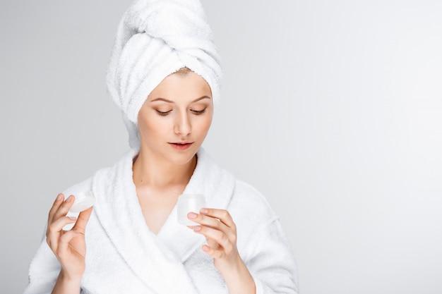 Tierna mujer rubia con una toalla de baño sobre el cabello mostrando crema