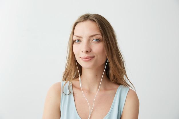 Tierna niña bonita soñadora escuchando música en auriculares.
