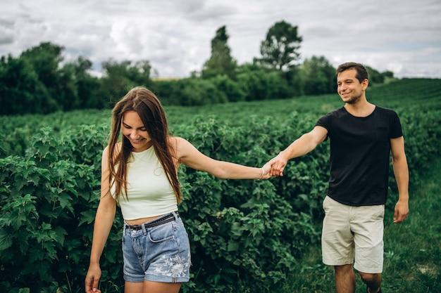 Una tierna pareja amorosa caminando en un campo de grosella. una mujer sonriente con cabello largo conduce a un hombre, sosteniendo su mano