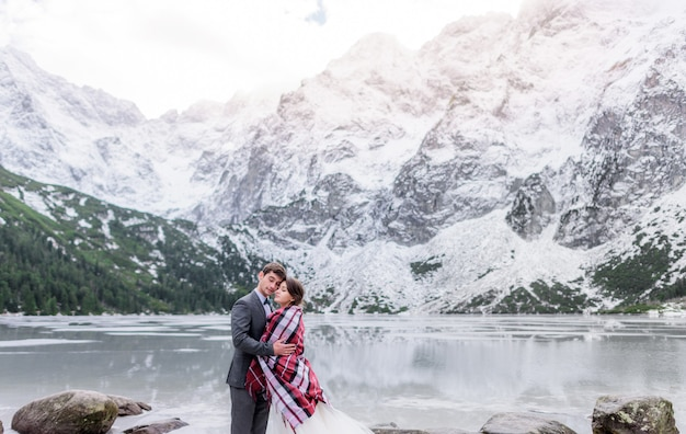 Tierna pareja cubierta con una manta enamorada congelada en las montañas de invierno frente al lago congelado