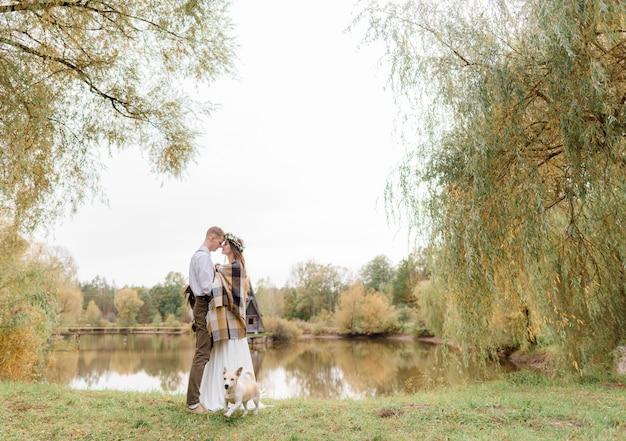 Tierna pareja de enamorados en el parque de otoño con un perro está de pie casi besándose cerca del lago