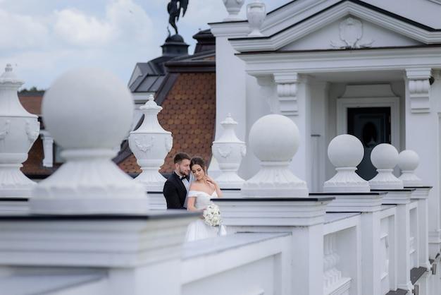Tierna pareja de enamorados está de pie al aire libre cerca del edificio el día de la boda