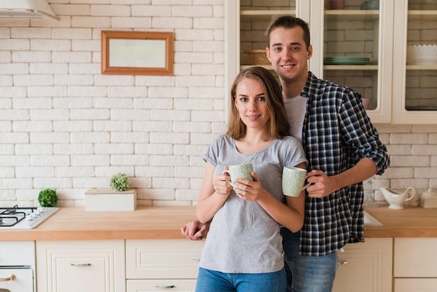 Tierna unión pareja bebiendo cerveza y de pie en la cocina