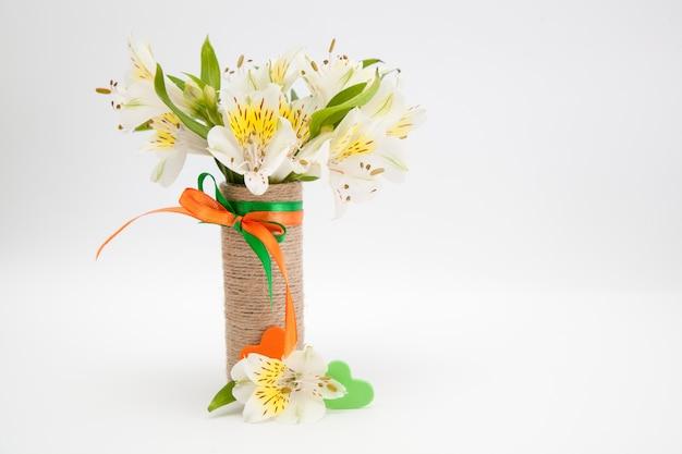 Tiernas flores blancas pequeñas orquídeas en un jarrón.