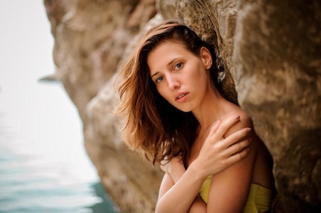 Tierno retrato de mujer joven pelirroja en traje de baño amarillo de pie cerca de la roca del mar