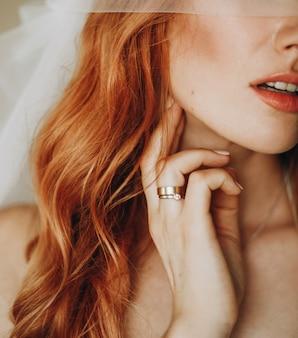 Tiernos labios y piel de encantadora novia con pelo rojo rizado.