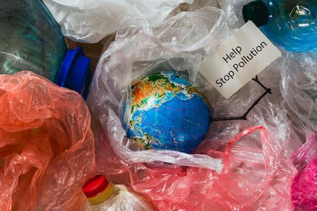 Tierra en bolsas de plástico tiene tarjeta con la ayuda de inscripción