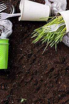 Tierra contaminada con basura de bolsas, vasos y utensilios de plástico.