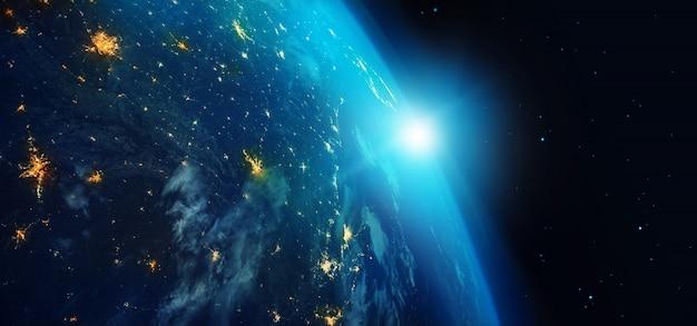 Tierra desde el espacio por la noche con luces de la ciudad y un amanecer azul sobre fondo de estrellas.
