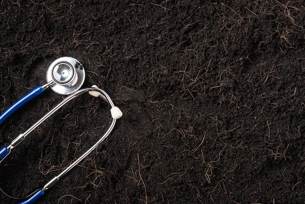 Tierra negra para fondo vegetal y estetoscopio médico.