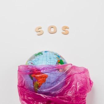 Tierra en plástico al lado de letras diciendo sos