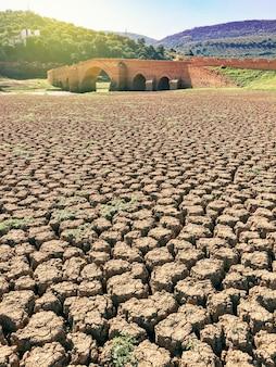 Tierra seca y agrietada en un pantano sin agua y un puente en la parte inferior