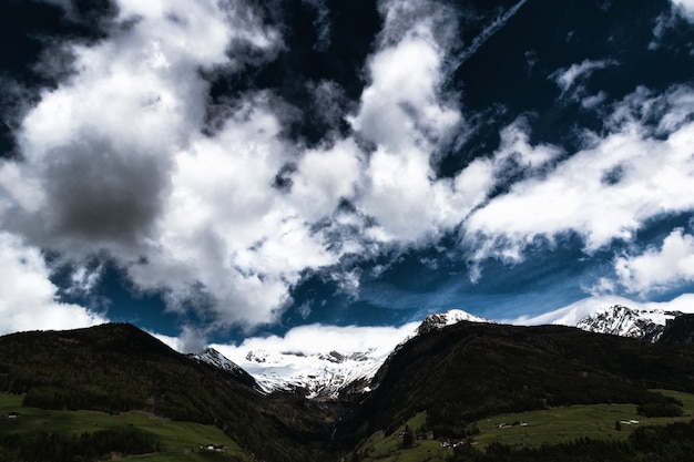 Tierra verde cerca de montañas bajo el cielo