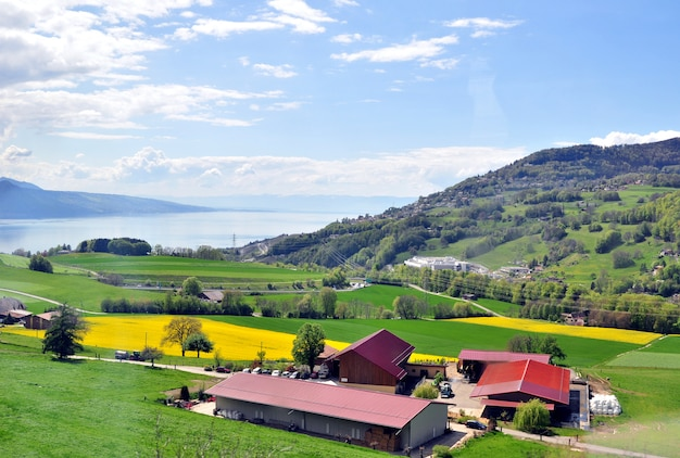 Tierras de cultivo a orillas de un lago alpino rodeado de montañas