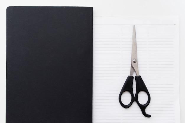 Tijeras en el bloc de notas en blanco