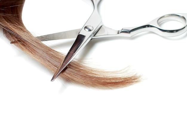 Tijeras y cabello castaño aislado sobre fondo blanco.