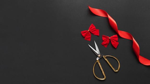 Tijeras cerca de lazos rojos y cinta.