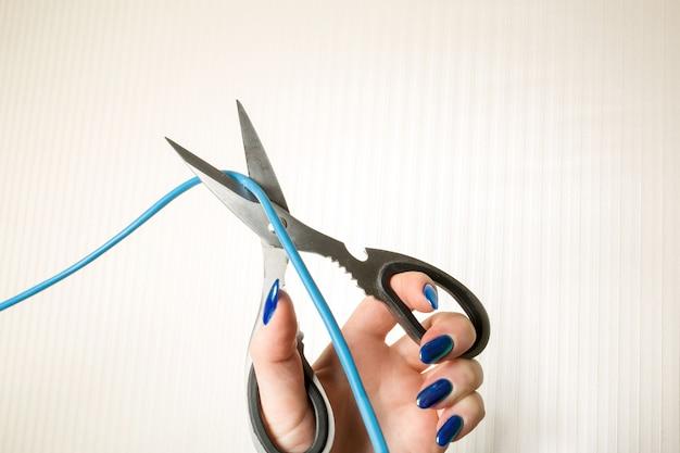 Las tijeras cortan el cable de conexión sobre un fondo beige
