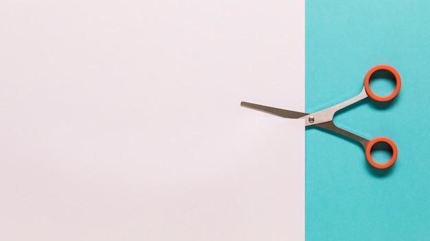 Tijeras para cortar papel blanco.