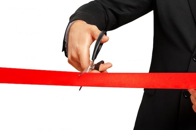 Las tijeras están cortando cinta roja o cinta. aislado en blanco