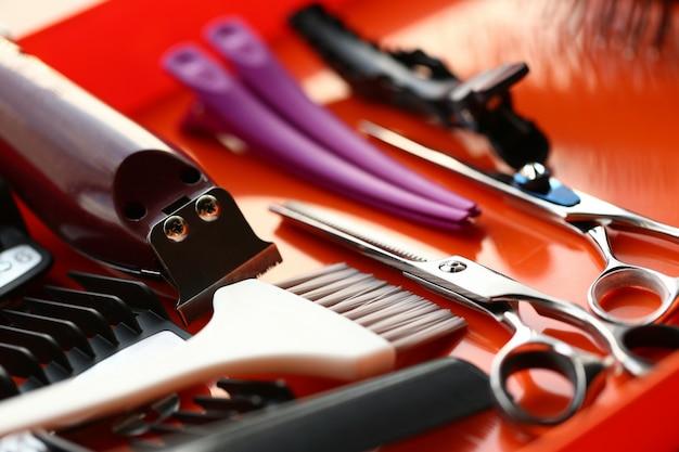 Tijeras y herramienta de peluquería sobre fondo rojo.