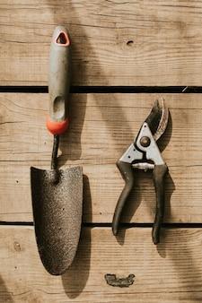 Tijeras de jardinería y paleta sobre una mesa de madera flatlay