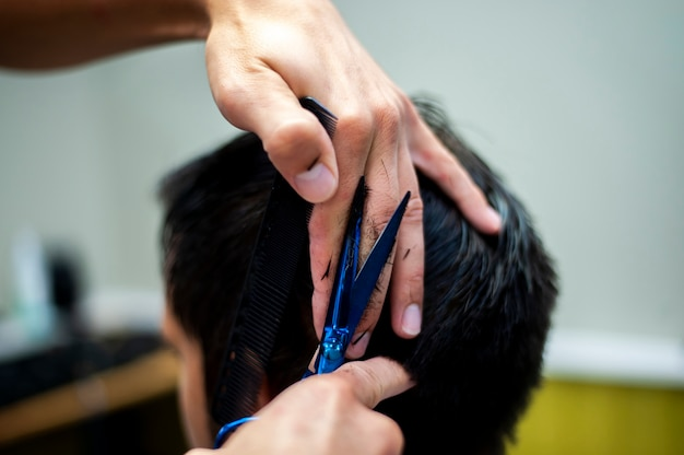 Tijeras y manos sobre el cabello del cliente
